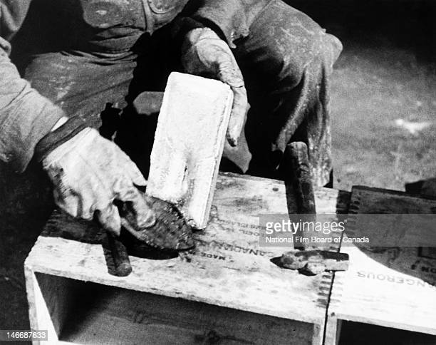 View of a man cleaning with a brush a freshly made gold bullion bar inside a gold refinery Val d'Or Quebec Canada 1949 Photo taken during the...