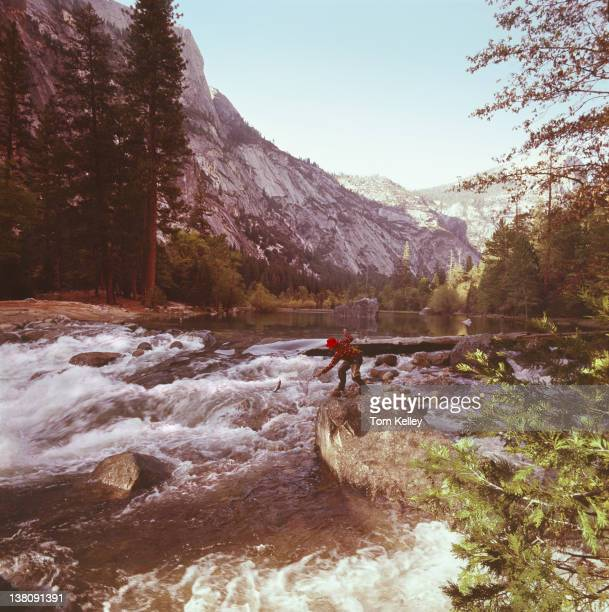 View of a man fly fishing near rapids in Yosemite National Park 2001