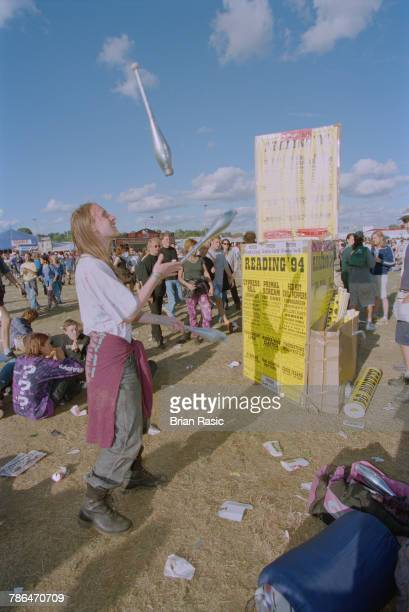 View of a man juggling with clubs as rock fans and festival goers relax between acts on stage at the 1994 Reading Festival in England on 27th August...