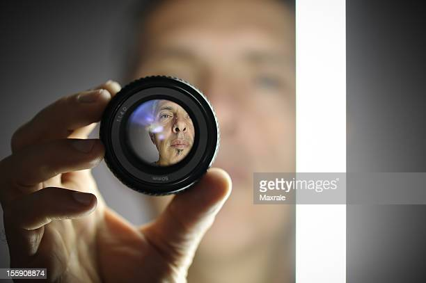 A view of a man looking through a camera lens
