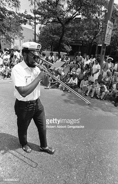 View of a man playing a trombone while walking during the Bud Billiken Day parade, Chicago, Illinois, mid to late 1960s .
