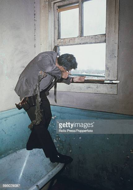 View of a man possibly a press photographer using a mop as a prop for a rifle to mimic the shooting position taken by the assassin who shot the civil...