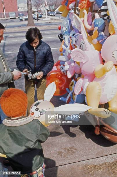 View of a man purchasing an inflatable bunny doll for a child from a street vendor on Woodhaven Boulevard in the Rego Park neighborhood Queens New...
