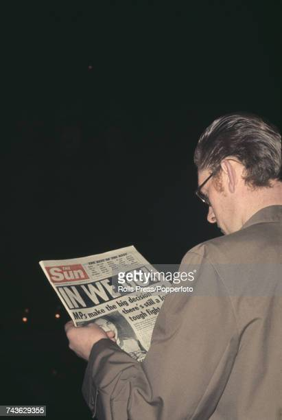 View of a man reading the front page of the Sun newspaper with the headline proclaiming 'In We Go' following the United Kingdom Parliament vote in...