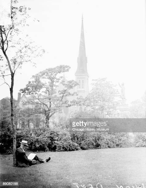 View of a man sitting against a tree on a lawn in Union Park in Chicago Illinois holding a piece of paper on his lap 1929 A church and a statue are...