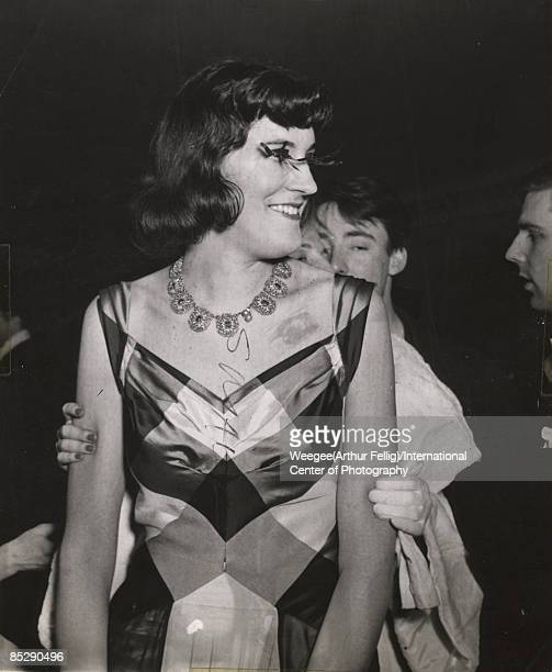 View of a man smiling while dressed and made up as a woman with others at a Greenwich Village costume ball ca1950s Photo by Weegee/International...