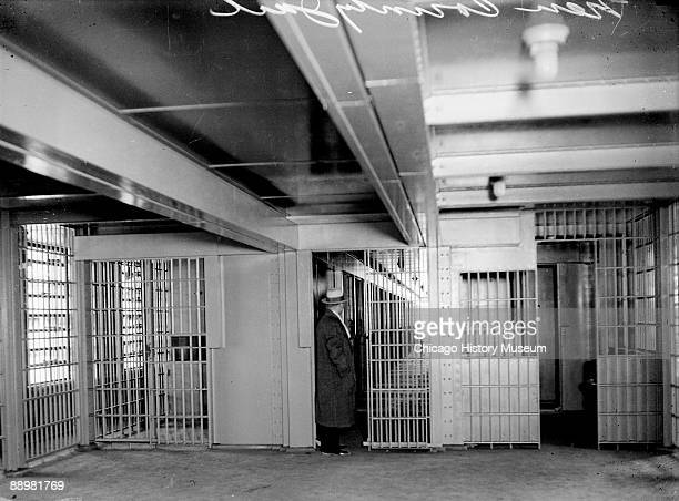 View of a man standing in between open doors made with iron bars in a large room in the Criminal Court building located at 54 West Hubbard Street in...