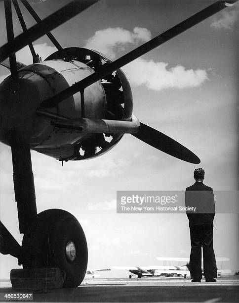 View of a man standing next to an airplane with other airplanes visible in the distance New York 1930