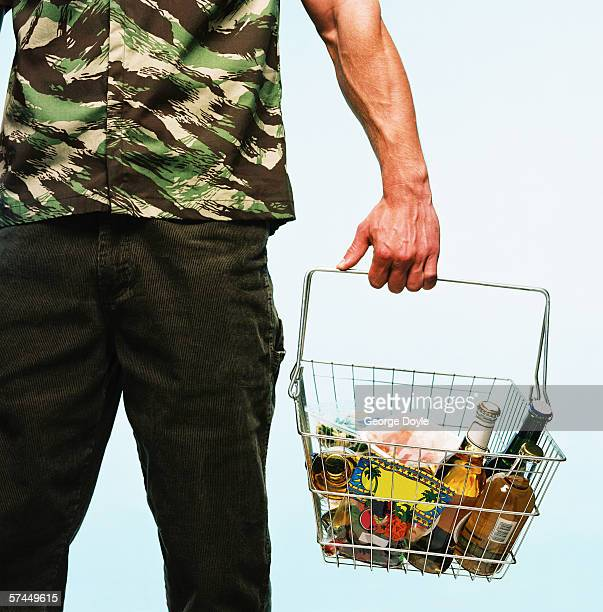 view of a man standing with goods in a shopping basket