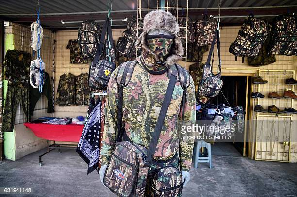 View of a mannequin decked out in camouflage clothing and gear sold to migrants at a store in the town of Altar in Sonora state Mexico on January 12...