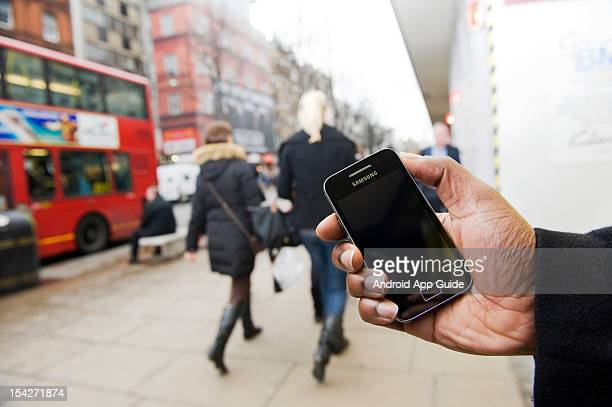 A view of a man's hand as he uses a Samsung Galaxy Ace smartphone on the streets of London during a shoot for Android App Guide February 11 London