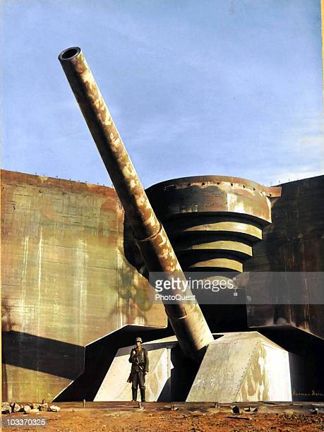 View of a massive piece of German coastal artillery in a concrete casement on the Atlantic Wall France early 1940s A German soldier stands in front...