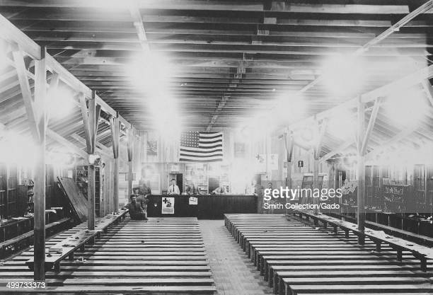 View of a meeting room at Carlstrom Field military base full of long rows of wooden benches and decorated with an American flag bright lights and...