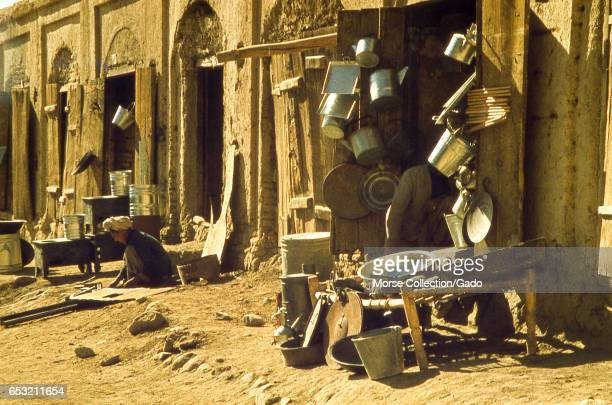 View of a merchant's boy assistant working outside the market stalls of the Bamiyan bazaar, in the Hazarajat region of Afghanistan, November, 1975. .