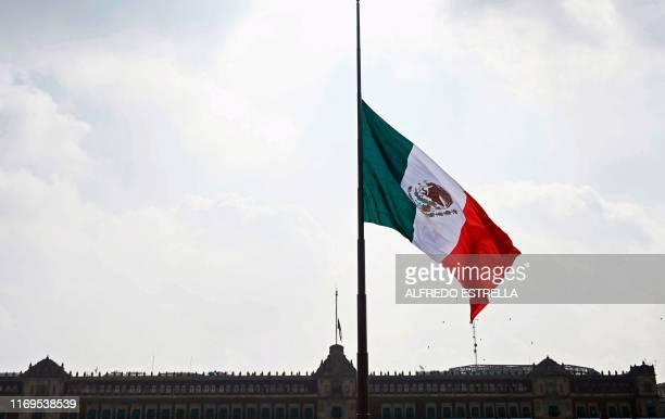 View of a Mexican national flag with the National Palace in the background at the Zocalo square in Mexico City on September 19 as Mexico marks the...
