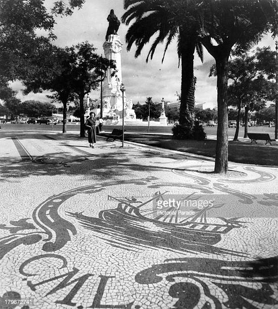 A view of a mosaic sidewalk and stately palm trees on the border of Boulevard The Avenida da Liberdade in Lisbon Portugal