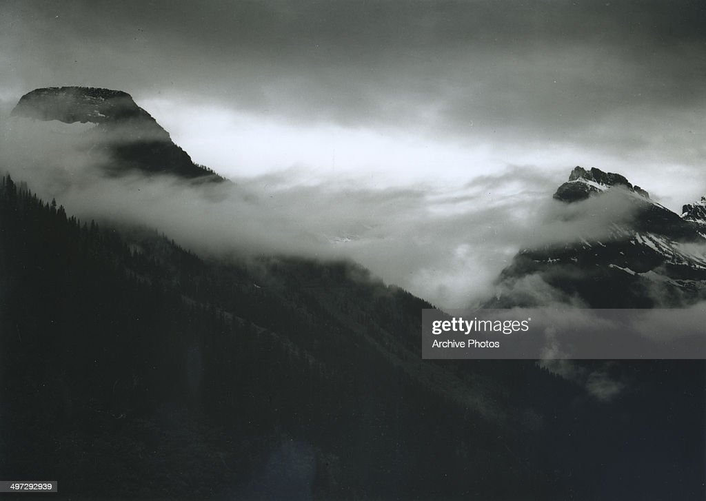 View of a mountain partially covered with clouds in Glacier National Park, Montana, 1941.