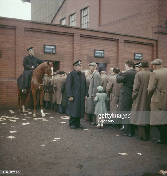 View of a mounted policeman on a police horse helping fellow police officers to control a crowd of football supporters queuing outside Ibrox Stadium...