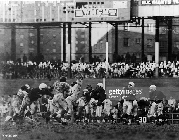 View of a muddy game between professional football teams the New York Giants playing at home against the Chicago Cardinals at the Polo Grounds New...