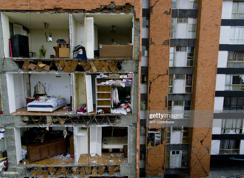 TOPSHOT - View of a multy-story building damaged during the September 19 earthquake, at one of Mexico City's most fashionable neighbourhoods on September 28, 2017. More than a week after an earthquake that killed more than 300 people, a shaken Mexico was torn between trying to get back to normal and keeping up an increasingly hopeless search for survivors. /