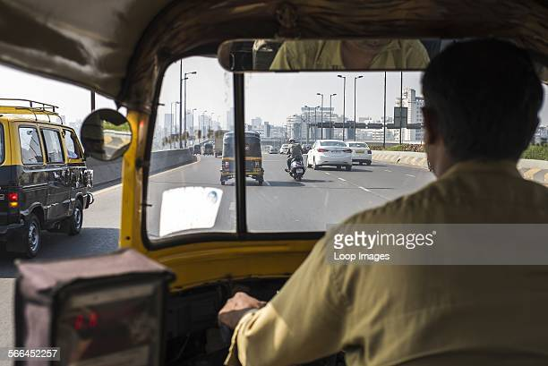 A view of a Mumbai road over the shoulder of an autorickshaw driver