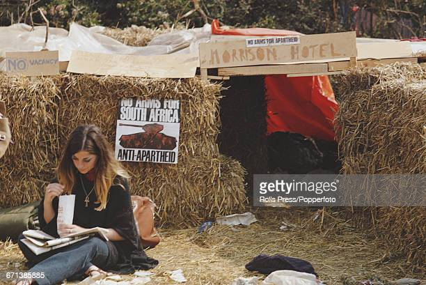 View of a music fan festival goer and camper sitting on the ground outside a temporary shelter made from hay bales and named Morrison Hotel during...