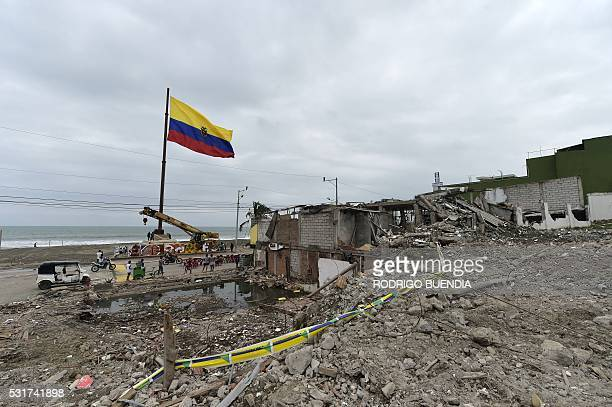 View of a national flag near rubble in Pedernales Ecuador on May 16 a month after a 78 magnitude earthquake rocked the city A total of 660 people are...