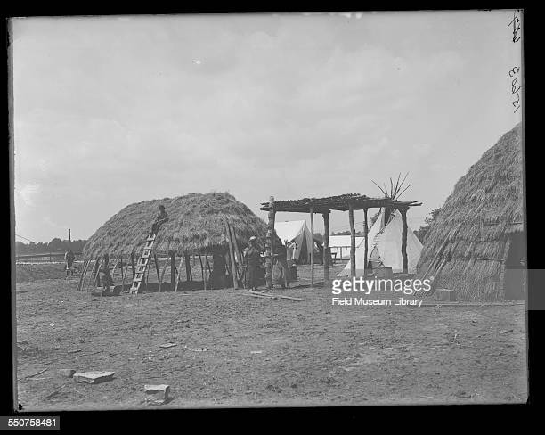 View of a Native American Wichita hut with people around it a young man on the roof and a wood ladder leaning against lodge at the Louisiana Purchase...