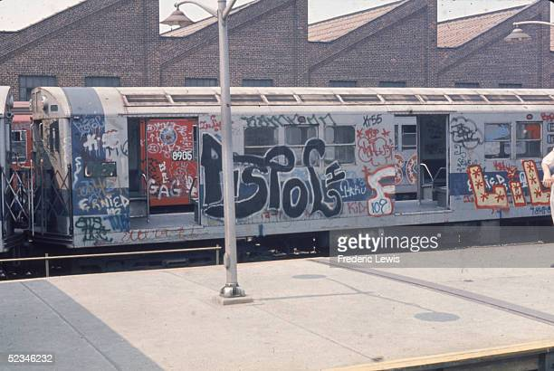 View of a New York City subway train car covered in graffiti and park with all its doors open in an unidentified station New York 1980s The train is...