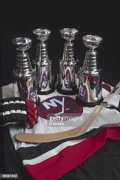 View of a New York Islanders jersey upon which stand four mini Stanley Cups a glove and a hockey stick 1980s Between 1980 and 1983 the Islanders won...