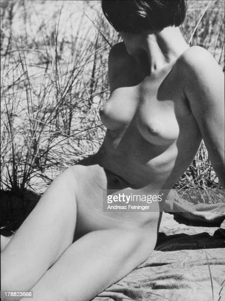 View of a nude female figure looking away seated on the ground 1932