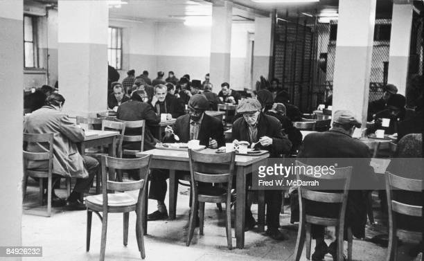 View of a number of homeless men as they eat a meal in the cafeteria of the Municipal Lodging House New York New York February 24 1967