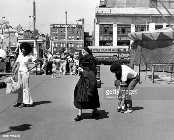 View of a nun among others as she walks at Brooklyn's Coney Island amusement park New York New York 1973
