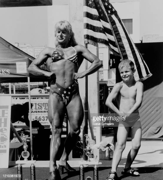 View of a pair of contestants, a woman in a 'stars and stripes' bikini and a young boy, both posing, during a Muscle Beach Venice bodybuilding...