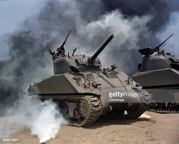 View of a pair of M4 Sherman tanks as they manouver through smoke during a training exercise July 1942