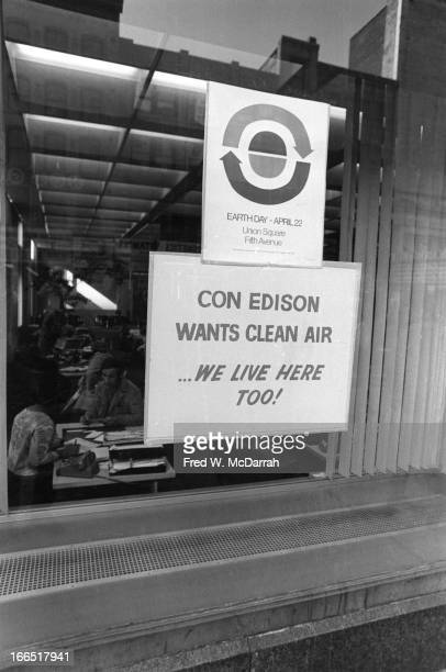 View of a pair of signs in a window one a flyer advertising Earth Day and the other reading 'Con Edison Wants Clean Air…We Live Here Too' New York...
