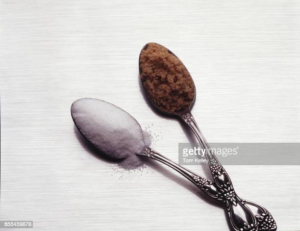 View of a pair of spoons one with granulated white sugar and one with brown sugar on a white surface California 2016