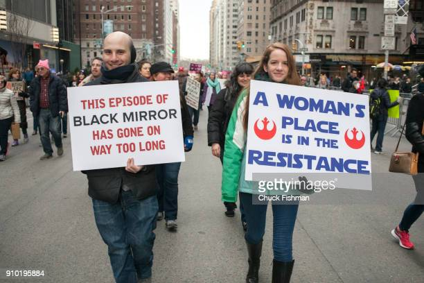 View of a pair of unidentified demonstrators both with signs on Sixth Avenue during the Women's March on New York New York New York January 20 2018...
