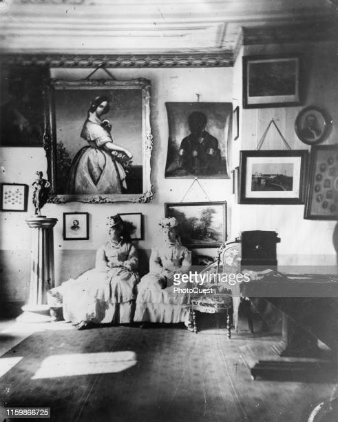 View of a pair of unidentified women as they sit in a photo studio Iowa City Iowa circa 1870