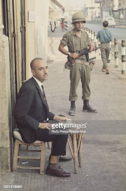View of a Palestinian man seated on a street drinking a cup of coffee as a member of the Israeli Defense Forces watches from behind in the Israeli...