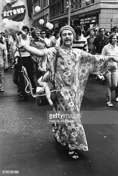 View of a paradegoer dressed in a flowerprint muumuu as he walks in the second annual Stonewall anniversary march then known as Gay Liberation Day...