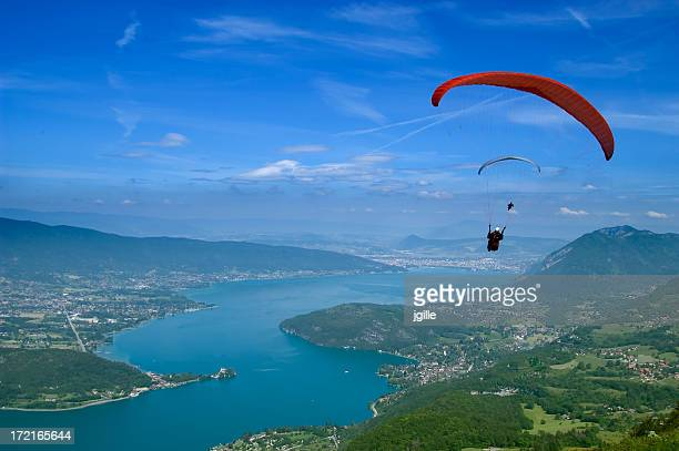 a view of a paraglider on a beautiful landscape - lake annecy stock photos and pictures