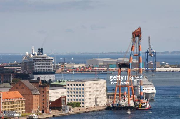 View of a part of Copenhagen harbor and the waterfront with some cruise liners, buildings and cranes