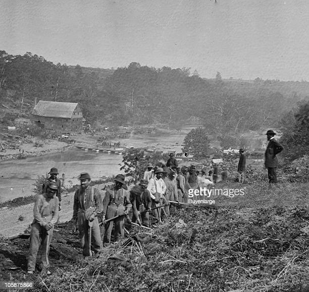 View of a party of the 50th New York Engineers building a road on the south bank of the North Anna River with a general headquarters wagon train...