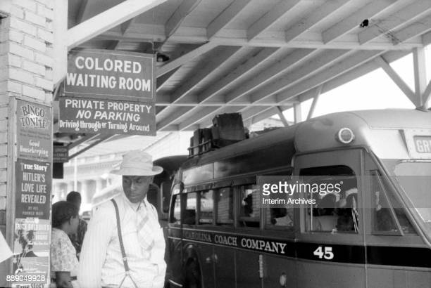 View of a passengers under a sign that reads 'Colored Waiting Room' at a bus station , Durham, North Carolina, 1940. Several buses, one from the...