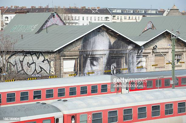 A view of a photograph posted on a wall by French graffiti artist and selfcoined photograffeur JR is pictured behind trains in Berlin on April 16...