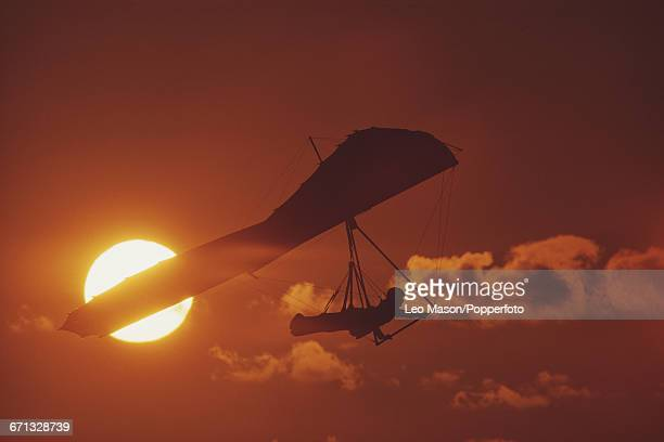 View of a pilot suspended under a hang glider as it flies in front of the setting sun over the town of La Jolla near San Diego in California in 1980
