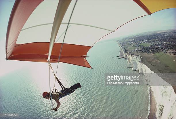 View of a pilot suspended under a hang glider as it flies over the cliffs of Beachy Head and the English Channel in East Sussex England in 1977