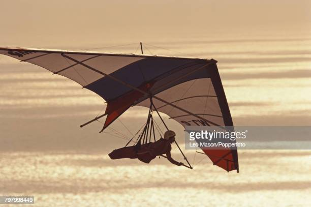 View of a pilot suspended under a hang glider as it flies over the Pacific Ocean near the coastal town of La Jolla San Diego in California in 1981