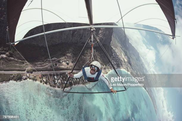 View of a pilot suspended under a hang glider as it flies over the coastline at Makapu'u on the island of O'ahu in Hawaii in 1979